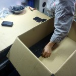 A worker stands at a press and puts parts into a box. He pulls the next item out of the press, which is already cooled, clips the plastic runner off, verifies that it fits in the master part, and puts it in the box. Then he grabs the next part and repeats the process. The runners can be chipped and put back in the hopper, so injection molding has very little waste.