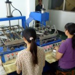 Two women take the material and run in through a machine which puts bends in the packaging around the card. The product will be inserted later.